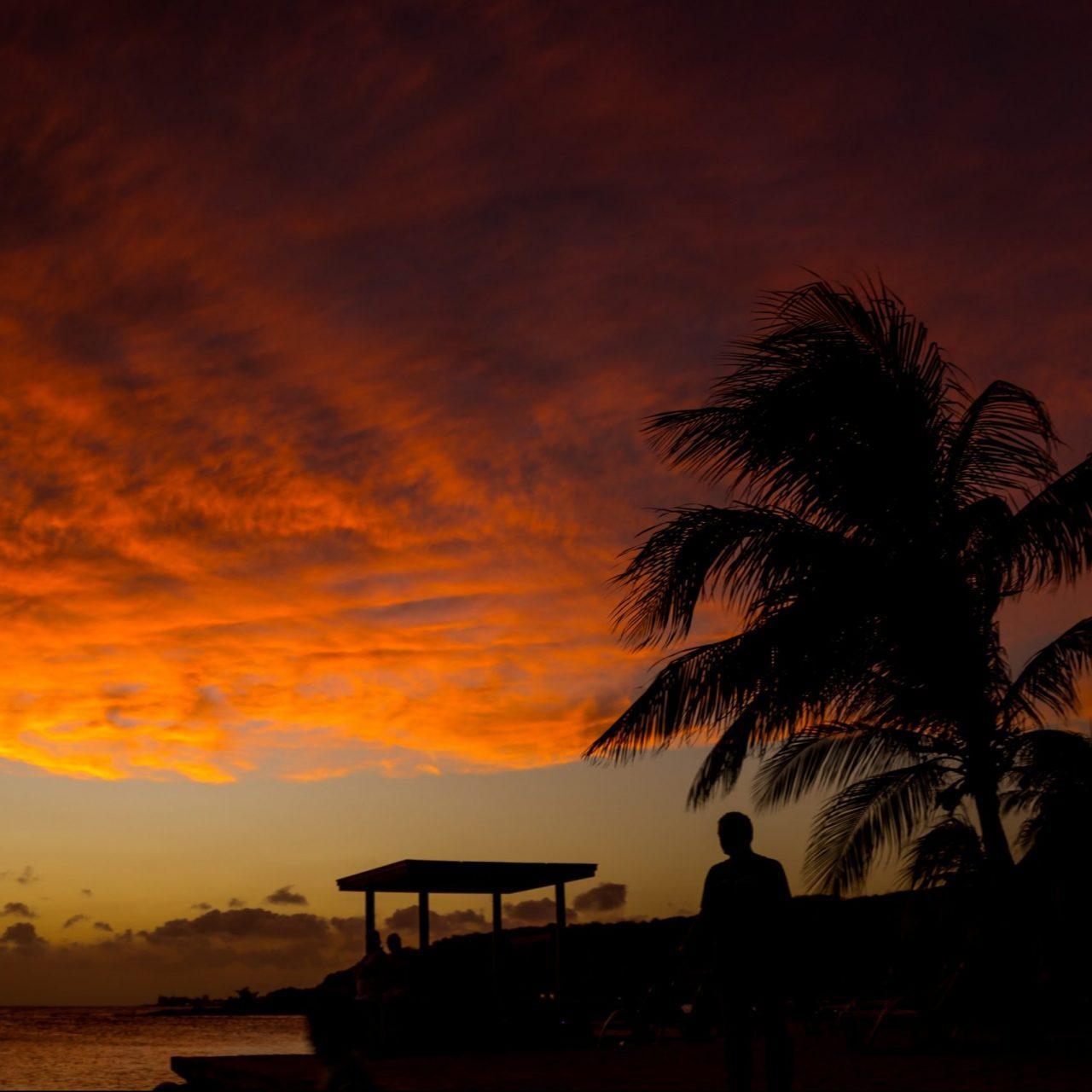 Karibialainen ranta ja henkilö silhuetteinä auringonlaskua vasten